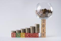 Комплект копилки на деревянных блоках 2017 с золотыми монетками в опарнике денег Стоковые Фотографии RF