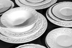 Комплект красивых белых керамических плит сброса обедающего на черной предпосылке Стоковая Фотография