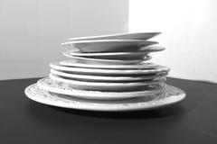 Комплект красивых белых керамических плит сброса обедающего на черной предпосылке Стоковые Фото