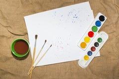 Комплект красок акварели, щеток для красить и пустого листа белой бумаги sketchbook Стоковые Изображения