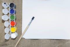 Комплект красок акварели, щеток для красить и пустого листа белой бумаги sketchbook Стоковые Фото
