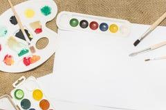 Комплект красок акварели, щеток для красить и пустого листа белой бумаги sketchbook Стоковая Фотография RF