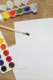 Комплект красок акварели, щеток для красить и пустого листа белой бумаги sketchbook Стоковое Изображение RF