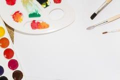 Комплект красок акварели, щеток для красить и пустого листа белой бумаги sketchbook Стоковое Фото