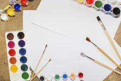 Комплект красок акварели, щеток для красить и пустого листа белой бумаги sketchbook Стоковые Фотографии RF