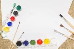 Комплект красок акварели, щеток для красить и пустого листа белой бумаги sketchbook Стоковая Фотография