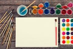 Комплект красок акварели, щеток для красить и пустой белой бумаги Стоковая Фотография RF