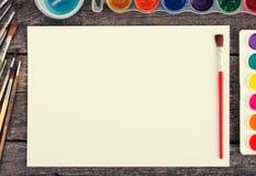 Комплект красок акварели, щеток для красить и пустой белой бумаги Стоковые Изображения
