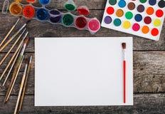 Комплект красок акварели, щеток для красить и пустой белой бумаги Стоковые Фотографии RF
