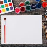 Комплект красок акварели, щеток для красить и пустой белой бумаги Стоковое фото RF