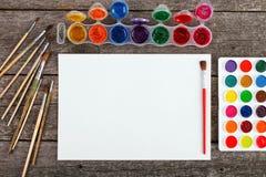 Комплект красок акварели, щеток для красить и пустой белой бумаги Стоковое Фото