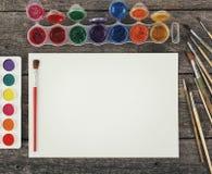 Комплект красок акварели, щеток для красить и пустой белой бумаги Стоковое Изображение RF
