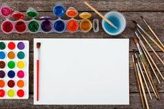 Комплект красок акварели, щеток для красить и пустой белой бумаги Стоковая Фотография