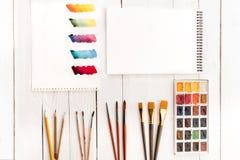 Комплект красок, различных щеток, пустой тетради и красочных brushstrokes на бумаге Стоковые Изображения