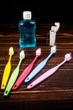 Комплект красочных toothbrushs с mountwash и зубоврачебной зубочисткой на b Стоковая Фотография