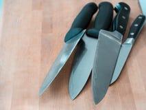 Комплект ножей на деревянной разделочной доске, подготавливает для варить Стоковые Фотографии RF