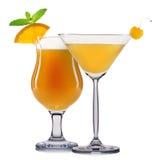 Комплект оранжевых коктеилей с украшением от плодоовощей и красочной соломы изолированных на белой предпосылке Стоковые Фотографии RF
