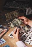 Комплект долларов в карманн через лупу Стоковые Фото
