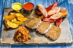 Комплект пива Хлеб, сосиска, картошки, капуста и соусы на деревянной доске Стоковые Изображения