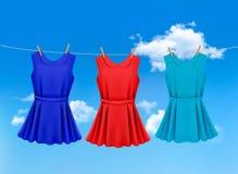 Комплект покрашенных платьев вися на веревке для белья иллюстрация вектора