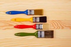 Комплект покрашенных щеток для ремонтов на деревянной предпосылке Стоковая Фотография RF