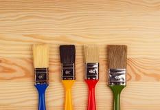 Комплект покрашенных щеток для ремонтов на деревянной предпосылке Стоковое Изображение RF