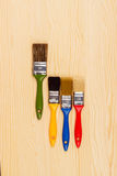 Комплект покрашенных щеток для ремонтов на деревянной предпосылке Стоковое Фото