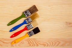 Комплект покрашенных щеток для ремонтов на деревянной предпосылке Стоковое Изображение