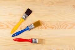 Комплект покрашенных щеток для ремонтов на деревянной предпосылке Стоковое фото RF