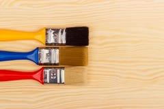 Комплект покрашенных щеток для ремонтов на деревянной предпосылке Стоковые Фотографии RF