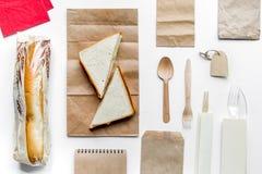 Комплект поставки с бумажными сумками и сандвич на белом взгляд сверху предпосылки Стоковое Изображение