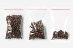 Комплект 3 ПУСТЫЕ, ПОЛОВИННЫХ И ПОЛЬНОСТЬЮ пластичных прозрачных сумок молнии при кофейные зерна изолированные на белизне Модель- Стоковые Фото