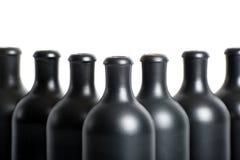 Комплект пустых черных бутылок глины на белом конце-вверх предпосылки Стоковое Фото