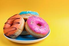Комплект плиты donuts в поливе на оранжевой предпосылке Стоковое Изображение RF