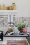 Комплект плит и блюда на счетчике в комнате кухни Стоковая Фотография