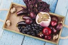 Комплект различных фиолетовых свежих сырцовых овощей и плодоовощей в деревянном подносе Стоковое фото RF