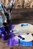 Комплект различных щеток и акрилов, который нужно покрасить разбросал на темный деревянный стол Предпосылка рабочего места художн Стоковая Фотография RF