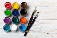 Комплект различных щеток и акрилов, который нужно покрасить разбросал на темный деревянный стол Предпосылка рабочего места художн Стоковые Изображения RF