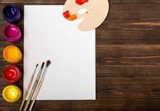 Комплект различных щеток и акрилов, который нужно покрасить разбросал на темный деревянный стол Предпосылка рабочего места художн Стоковые Фотографии RF