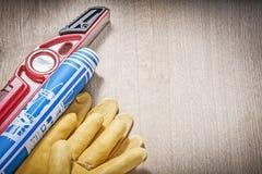 Комплект светокопий уровня конструкции перчаток безопасности голубых на woode Стоковая Фотография