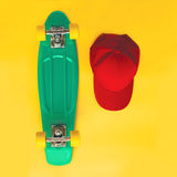 Комплект способа Скейтборд и бейсбольная кепка над желтой предпосылкой, взгляд сверху Стоковые Фото