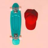 Комплект способа Скейтборд и бейсбольная кепка на розовой предпосылке Стоковое Изображение