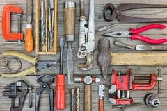 Комплект старых ржавых инструментов и оборудования для ручной работы на серой древесине Стоковые Изображения RF
