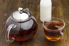 Комплект стеклянных чайника, чашка и бутылки молока Стоковые Изображения
