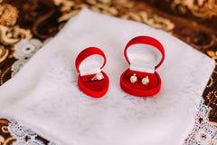 Комплект стильных ювелирных изделий женщин: серьги и кольцо пальца с жемчугами в красных коробках для каждого на белой silk ткани Стоковое Изображение RF