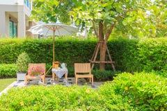 Комплект чая на деревянном столе под белым зонтиком в саде Стоковое Изображение RF