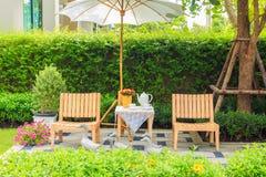 Комплект чая на деревянном столе под белым зонтиком в саде Стоковая Фотография RF