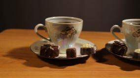 Комплект чая на таблице с конфетой шоколада сток-видео