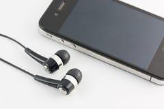 Комплект черного оборудования наушника и Smartphone изолированный на белом ба Стоковое Изображение RF