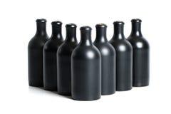 Комплект штейновых черных бутылок глины на белой предпосылке Стоковые Изображения